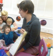 Katie reading a large open praise project story to a toddler group